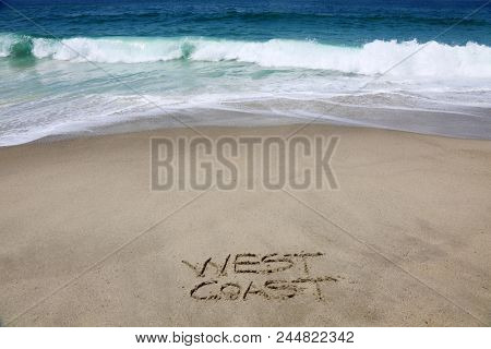 WEST COAST. The words West Coast written in sand on the beach.