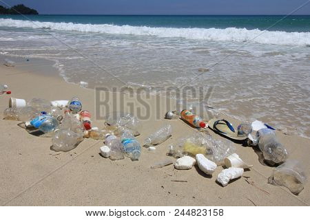 KUDAT, MALAYSIA - 06 JUNE 2018: Plastic pollution on beach. Plastic bottles, bags and other rubbish dumped on beach and in ocean.