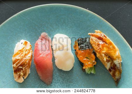 Fresh japanese sushi with fatty tuna belly, scallops, salmon roe and eel on a blue pate top view