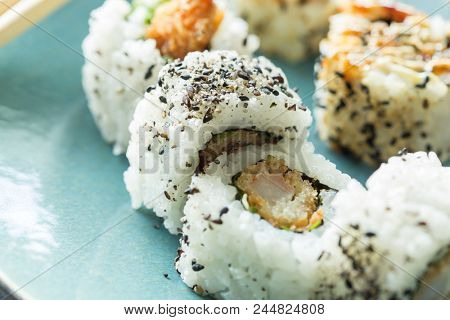 Tempura prawns in sushi rice with seaweed and sesame on a blue plate