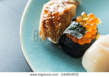 Fresh japanese sushi with eel, salmon roe and scallops prepared on a blue plate