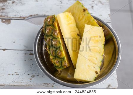 Slices of pineapple on a metal plate on a rustic white background