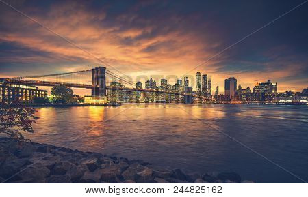 New York City at sunset. NYC famous postcard place at Brooklyn Bridge park with Brooklyn Bridge in front of image.