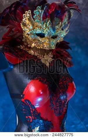Glamour, Red golden venetian carnival mask with feathers  on a draped red velvet theater curtain. Mask in the dark