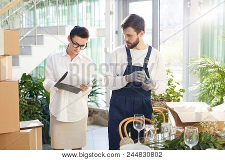 Serious concentrated female entrepreneur in glasses working with mover and examining consignment note while taking delivery of goods, bearded worker unpacking box with glasses