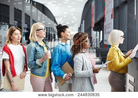 Group of multiethnic women in smart casual outfits standing in line while applying documents at registration for business event