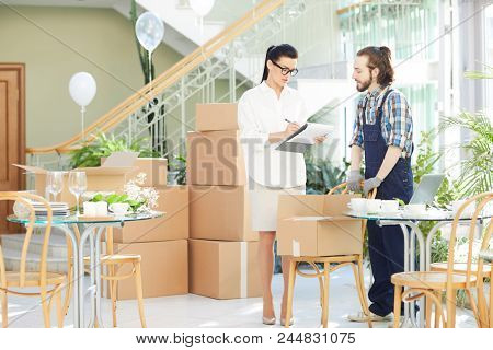 Serious confident restaurant manager in formalwear talking to moving company employee while examining checklist during unpacking delivered boxes