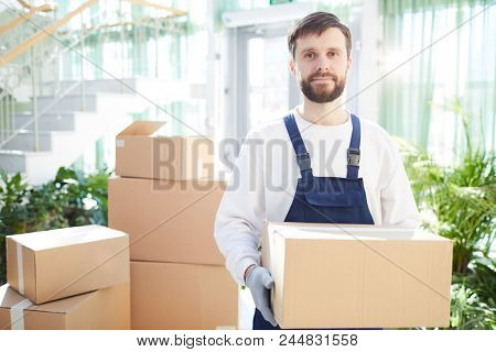 Serious confident handsome bearded moving company employee in overalls carrying heavy cardboard box and looking at camera in lobby, stack of boxes behind him