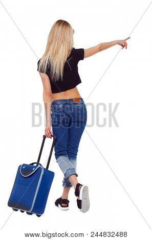Back view of  pointing woman with suitcase pointing. Standing young girl. Rear view people collection.  backside view of person. Isolated over white. A traveler with a blue suitcase in summer clothes