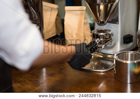 Close-up Image Of Female Barista Using Coffee-making Machine Making Of Espresso Pouring From Coffee
