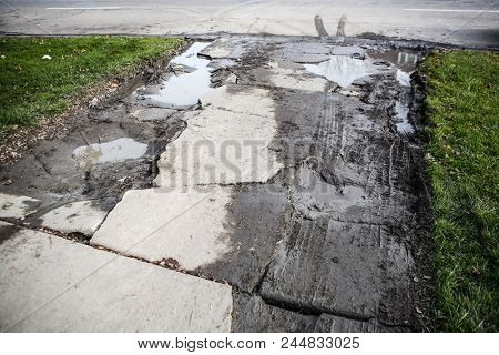 Broken damaged cement driveway with puddles