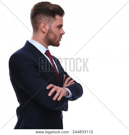 side view of confident businessman looking to side while standing on white background with hands crossed