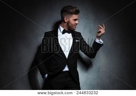 portrait of formal man in a black tuxedo looking at hand to side while snapping fingers. He is standing with a hand in pocket, leaning against a grey wall
