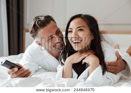 Photo of multiethnic couple caucasian man and asian woman wearing white bathrobe lying in home bedroom or hotel apartment with remote control in hand while watching tv