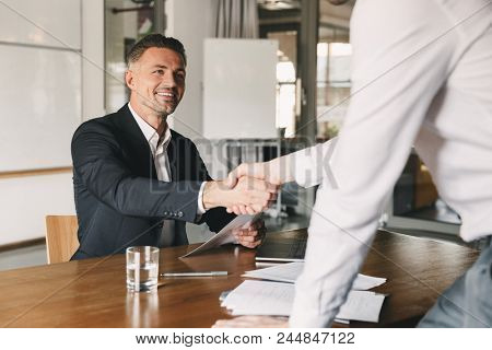 Business, career and placement concept - satisfied director man 30s smiling and shaking hands with male candidate who was recruited during interview in office