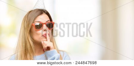 Young woman celebrates birthday with index finger on lips, ask to be quiet. Silence and secret concept
