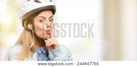 Young woman with bike helmet and earphones with index finger on lips, ask to be quiet. Silence and secret concept