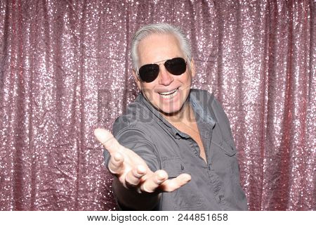 A happy middle aged man in a Photo Booth.   A happy man laughs, sings, and makes funny faces as he smiles while in a Photo booth at a Party. Party Time Photo Booth.