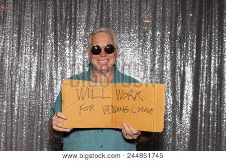 A happy middle aged man in a Photo Booth.   A happy man holds a sign that reads WILL WORK FOR WEDDING CAKE as he smiles while in a Photo booth at a Party. Party Time Photo Booth.