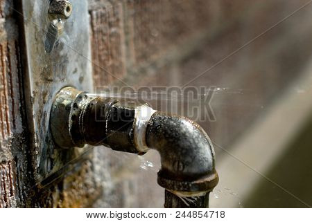 Leaky pipe with water spraying and squirting out faulty leaking