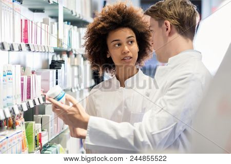 Dedicated female pharmacist talking with her experienced colleague about the attributes and side effects of a new medicine or pharmaceutical product for sale, in the pharmacy
