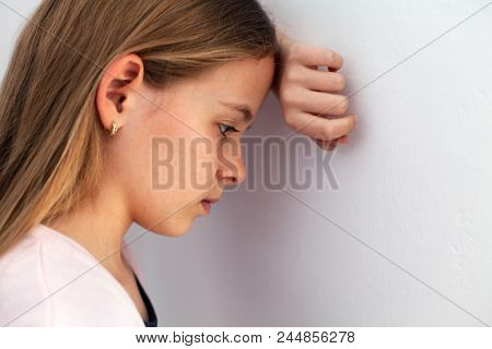 Young sad teenager girl propping her head against the wall - closeup portrait of pensive youngster