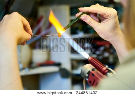 Close Up Of Elegant Female Hands Shaping Glass Beads Over Gas Torch While Making Beautiful Handmade
