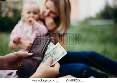 Earning Money For Family. Male Hand With Wallet And Us Dollar Bills At Family Blurred Background. Fi