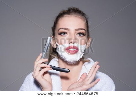 Girl on confident face wears bathrobe, grey background. Woman with face covered with foam holds straight razor in hand. Barber and shaving concept. Lady play with sharp blade of straight razor. poster