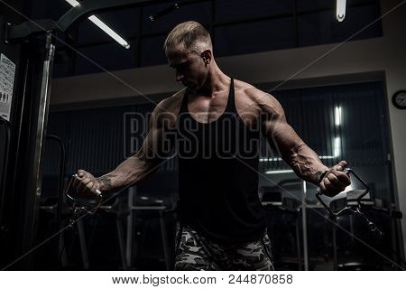 Muscular Tough Man In Gym In Crossover Machine, Shallow Depth Of Field