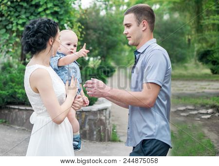 Portrait Of Young Family Pretty Mother Holding Small Son Baby Boy And Father In Green Summer Park. L