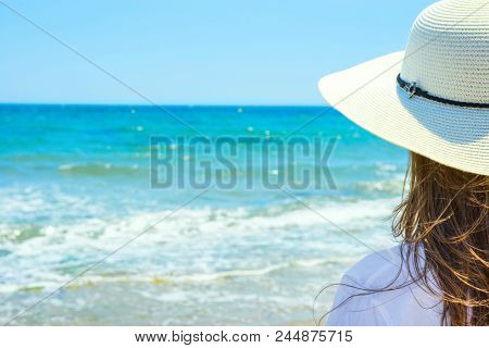 Young Attractive Caucasian Woman With Long Chestnut Hair In Hat Stands With Back On Sand Beach Looks