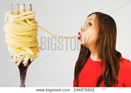 Young Girl Eats Huge Spaghetti From A Huge Fork On White Background.