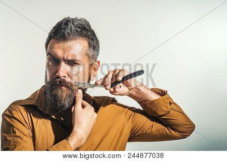 Barbershop Equipment. Bearded Man Having Shave In Barbershop With Razor Blade. Handsome Bearded Man,