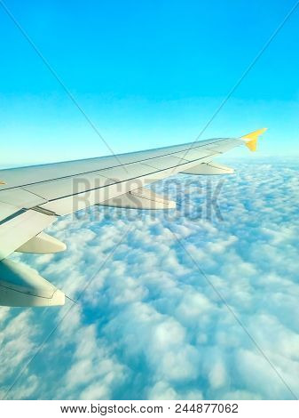 Real View From Window Of Flying Airplane Of Beautiful Scenic Cloudscape. Wing On Blue Sky Fluffy Clo