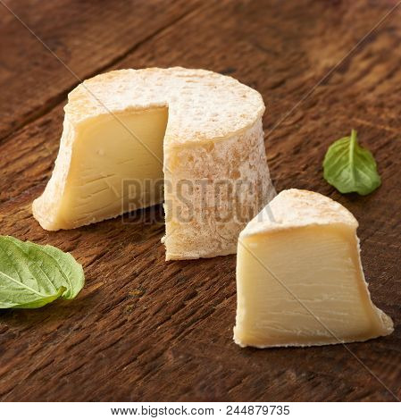 Crottin Cheese With Basil Leaves On Rustik Wooden Background