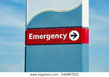Horizontal Close-up Shot Of A Hospital Emergency Room Sign.  Cloudy Sky Background.