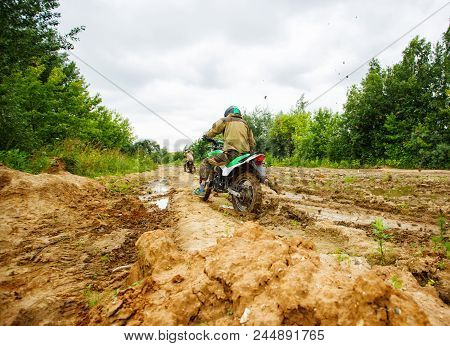 Motocross Racer Racing On The Off-road Circuit Mud Flying Through Air. Motorbike Rides Through The M