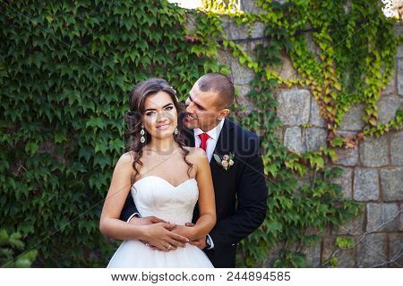 Bride And Groom Walking Around Buildings. Wedding Day. Holiday Clothes A