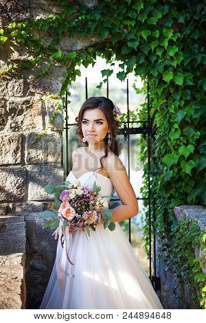 Beautiful Young Bride With A Bouquet Of Wedding Flowers. Holiday Dress