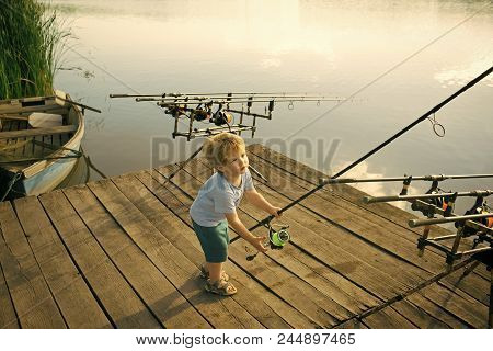 Fishing Gear. Fisher Boy With Fishing Rod On Wooden Pier. Fisher Child With Tackle On River Or Lake.