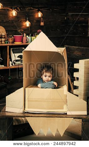 Children's Dreams Of Space. Kid Sit In Cardboard Hand Made Rocket. Boy Play At Home With Rocket, Lit