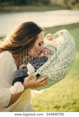Mother's Love. Mother Woman Kiss Baby Son In Basket On Natural Landscape