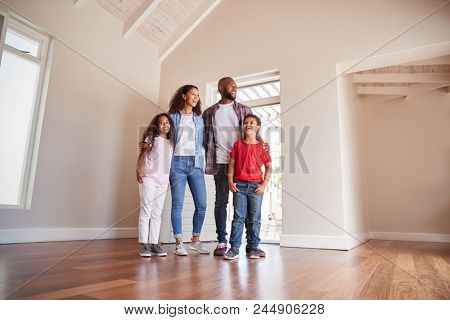 Family Opening Door And Walking In Empty Lounge Of New Home