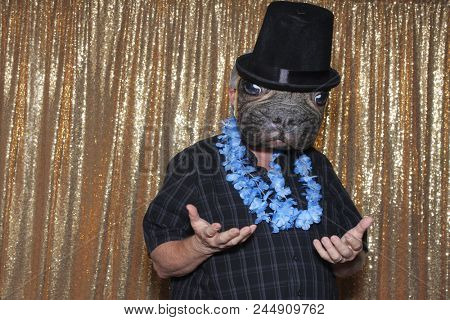 Dog Faced Boy in a Photo Booth. A man wears a Dog Face Mask and Top Hat while posing for his photo in a Photo Booth with a Gold Sequin background curtain.