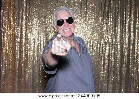 Man Posing in a Photo Booth. A handsome man poses and smiles while in a photo booth at a party or wedding.