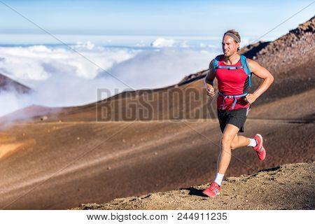 Trail running runner man on endurance run with backpack on volcano mountain. Ultra marathon race athlete on volcanic rocks path in mountains landscape. poster