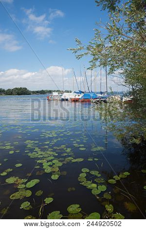 Landscape Chiemsee Lake With Colorful Moored Sailboats And Green Waterlily Leaves. Summer Idyll Bava