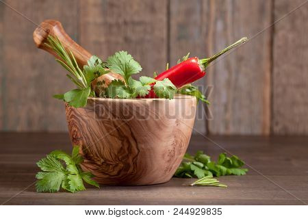 Wooden Mortar With Rosemary, Coriander, Thyme And Parsley. Warious Herbs On A Old Wooden Table .