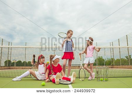 Portrait Of Group Of Girls As Tennis Players Holding Tennis Rackets Against Green Grass Of Outdoor C